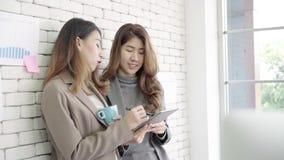 Dos estudiantes universitarios o compañeros de trabajo asiáticos jovenes de la empresaria que beben el café y que hablan en la of almacen de metraje de vídeo