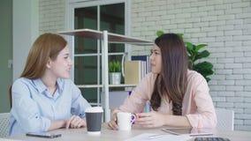 Dos estudiantes universitarios o compañeros de trabajo asiáticos jovenes de las mujeres que beben el café y que hablan en la ofic almacen de video