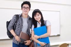 Dos estudiantes universitarios que se colocan en la clase Imagen de archivo