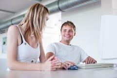Dos estudiantes universitarios que se divierten el estudiar junto Imagen de archivo libre de regalías