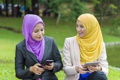 Dos estudiantes universitarios que tienen ideas de la discusión y del cambio mientras que se sienta en el parque Imágenes de archivo libres de regalías