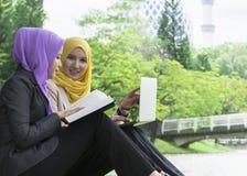 Dos estudiantes universitarios que tienen ideas de la discusión y del cambio mientras que se sienta en el parque Fotos de archivo libres de regalías