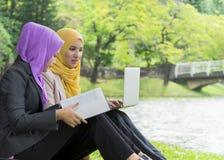 Dos estudiantes universitarios que tienen ideas de la discusión y del cambio mientras que se sienta en el parque Foto de archivo libre de regalías