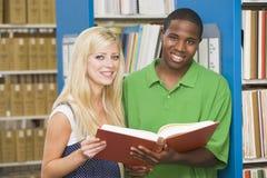 Dos estudiantes universitarios que trabajan en biblioteca Imágenes de archivo libres de regalías