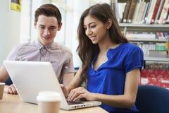 Dos estudiantes universitarios que trabajan en biblioteca usando el ordenador portátil Foto de archivo