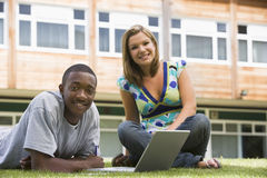 Dos estudiantes universitarios que usan la computadora portátil en césped del campus, fotografía de archivo libre de regalías
