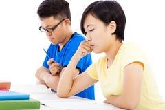 Dos exámenes jovenes de los estudiantes junto en sala de clase Fotos de archivo libres de regalías