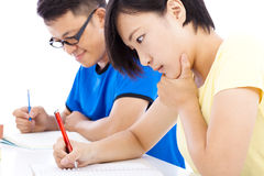 Dos exámenes jovenes de los estudiantes junto en sala de clase Imagen de archivo