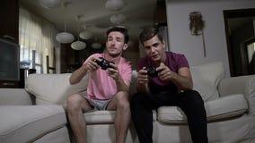 Dos excitaron a los amigos adolescentes que se divertían que jugaba a juegos de la TV con las palancas de mando inalámbricas en c almacen de metraje de vídeo