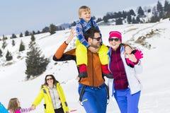 Dos familias con los niños que caminan en la nieve imagenes de archivo
