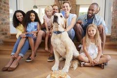 Dos familias que celebran cumpleaños del ½ s del ¿del dogï del animal doméstico en casa imagenes de archivo
