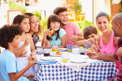 Dos familias que comen la comida en el restaurante al aire libre junto imagen de archivo