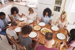Dos familias que dicen a Grace Before Eating Meal Together foto de archivo