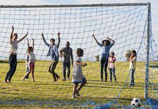 Dos familias que juegan a fútbol en el parque que celebra una meta fotos de archivo