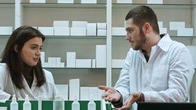 Dos farmacéuticos adultos que tienen conflicto, discutiendo problemas en la farmacia imágenes de archivo libres de regalías