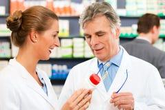 Dos farmacéuticos en la consulta de la farmacia imagen de archivo