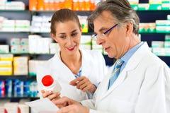 Dos farmacéuticos en la consulta de la farmacia Imágenes de archivo libres de regalías