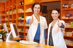 Dos farmacéuticos que detienen los pulgares Imágenes de archivo libres de regalías