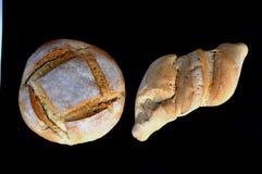 Dos fces de pan y de bollo que descansan sobre él Imagen de archivo