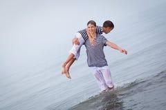 Dos felices, feliz, hermano juega en el mar Foto de archivo