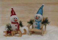 Dos felices muñecos de nieve con los trineos y en una silla Fotos de archivo