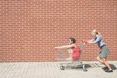 Dos femeninos divirtiéndose con un carro de la compra en el estacionamiento de la alameda Fotos de archivo libres de regalías
