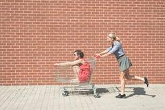 Dos femeninos divirtiéndose con un carro de la compra en el estacionamiento de la alameda Imágenes de archivo libres de regalías