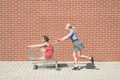 Dos femeninos divirtiéndose con un carro de la compra en el estacionamiento de la alameda Foto de archivo libre de regalías
