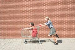 Dos femeninos divirtiéndose con un carro de la compra en el estacionamiento de la alameda Fotografía de archivo libre de regalías