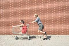 Dos femeninos divirtiéndose con un carro de la compra en el estacionamiento de la alameda Foto de archivo