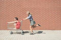 Dos femeninos divirtiéndose con un carro de la compra en el estacionamiento de la alameda Imagen de archivo
