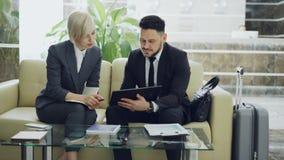 Dos femeninos y colegas masculinos del negocio que usan la tableta digital y hablando en el pasillo del hotel mientras que se sie almacen de metraje de vídeo