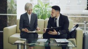 Dos femeninos y colegas masculinos del negocio que usan la tableta digital, libreta y discutiendo proyecto en el pasillo del hote metrajes