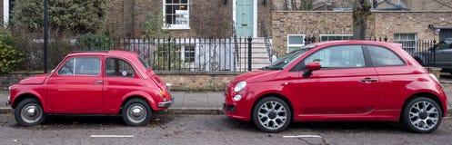 Dos Fiat rojo 500 clásicos Cinquecento aparcamiento en una calle residencial en Londres Reino Unido fotos de archivo libres de regalías