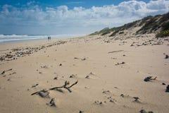 Dos figuras que caminan en una playa abandonada fotos de archivo