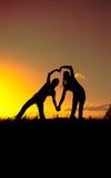 Dos figuras representan la forma del corazón contra el cielo en la puesta del sol Imagen de archivo libre de regalías