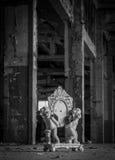 Dos figurillas de los ángeles que sostienen un reloj quebrado Fotografía de archivo