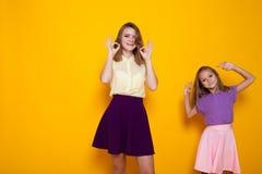 Dos fingeres y risas de la demostración de las muchachas Foto de archivo libre de regalías
