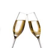 Dos flautas de champán con las burbujas de oro hacen alegrías en el fondo blanco Foto de archivo