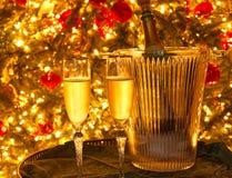 Dos flautas de champán y una botella del champán en un cubo de hielo de cristal delante de un árbol de navidad fotografía de archivo