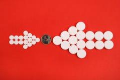 Dos flechas recogidas de tabletas se dirigen en una moneda Foto de archivo