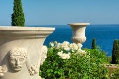 Dos floreros antiguos en parque hermoso al lado del mar Imagenes de archivo