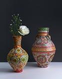 Dos floreros coloridos de la cerámica con la flor amarilla en fondo negro Imágenes de archivo libres de regalías