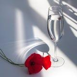 Dos flores rojas de la amapola en la tabla blanca con la luz y las sombras del sol del contraste y la copa de vino con el primer  foto de archivo