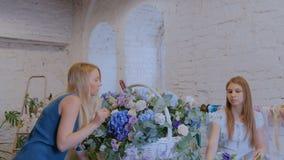 Dos floristas de las mujeres que hacen la cesta floral grande con las flores en la floristería metrajes