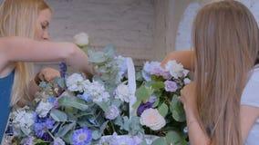 Dos floristas de las mujeres que hacen la cesta floral grande con las flores en la floristería almacen de video