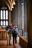 Dos fotógrafos que visitan el interior de la iglesia de la trinidad situado en W Imagenes de archivo
