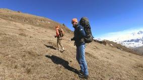 Dos fot?grafos de los turistas con las mochilas en sombreros y gafas de sol van encima de la colina en la hierba amarilla con las almacen de video