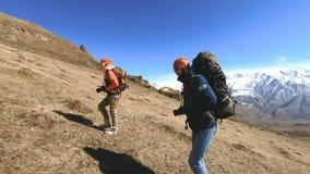 Dos fot?grafos de los turistas con las mochilas en sombreros y gafas de sol van encima de la colina en la hierba amarilla con las almacen de metraje de vídeo