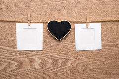 Dos fotos inmediatas en blanco con el corazón en fondo de madera Foto de archivo